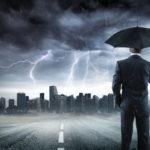 Businessman With Umbrella Looking Storm Over City