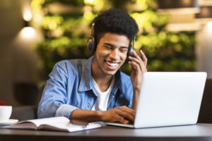 Student smiling in front of a computer