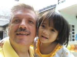 """Jim Altman poses for a photo with a Vietnamese orphan. This shot, he says, """"became our family vision for international adoption"""""""